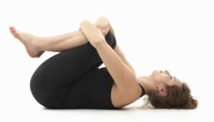 caucasian woman on the floor, in relaxed yoga pose, side view, dressed in black on white background